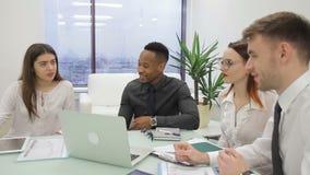 El grupo de trabajo está hablando positivamente mientras que se sienta en oficina moderna almacen de metraje de vídeo