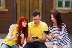 El grupo de tres amigos juega al videojuego móvil al aire libre fotos de archivo