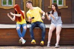 El grupo de tres amigos juega al videojuego móvil al aire libre, alzaprimando o imagenes de archivo
