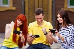 El grupo de tres amigos juega al videojuego móvil al aire libre, los ganadores fotos de archivo