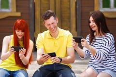 El grupo de tres amigos juega al videojuego móvil al aire libre, los wi de las muchachas fotografía de archivo libre de regalías