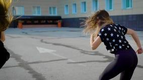 El grupo de tres bailarines de sexo femenino está bailando en yarda de edificio grande en una ciudad por la tarde del verano, cue metrajes