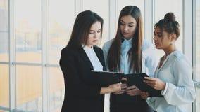 El grupo de tres hombres de negocios multiétnicos amistosos se coloca en el pasillo de la oficina, papeles del control, informe f