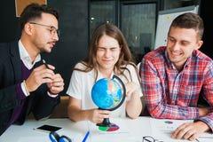 El grupo de tres personas jovenes con el globo elige el país para viajar a Foto de archivo