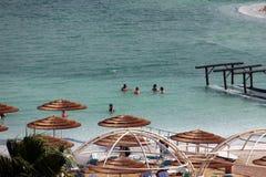 El grupo de turistas toma los tratamientos de aguas en el mar muerto Imagen de archivo libre de regalías