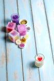 El grupo de velas del color pone en piso de madera Foto de archivo