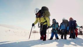 El grupo de viajeros en el uniforme lleno que entra en una línea recta a través de la nieve como consecuencia de sus paradas del  almacen de metraje de vídeo