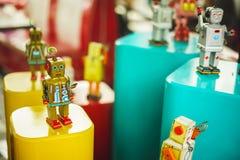 El grupo de vintage juega viejo color del robot Juguete de oro del robot del viejo vintage en un pedestal Robótica y diseño del p Fotografía de archivo