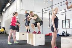 El grupo del entrenamiento entrena a saltos de la caja Foto de archivo libre de regalías