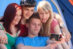 El grupo está tomando una foto mientras que la muchacha se pega la lengua hacia fuera Imagen de archivo libre de regalías