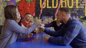 El grupo feliz de amigos tintinea los vidrios con el alcohol que se sienta en el restaurante metrajes