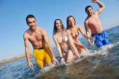 El grupo feliz de la gente joven se divierte en la playa Imagenes de archivo