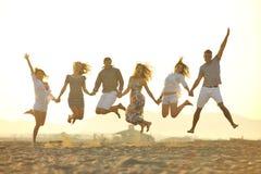 El grupo feliz de la gente joven se divierte en la playa Imagen de archivo libre de regalías