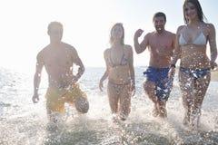 El grupo feliz de la gente tiene la diversión y funcionamiento en la playa Imagen de archivo