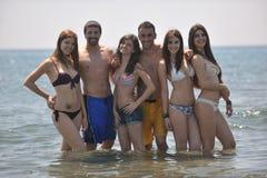 El grupo feliz de la gente tiene la diversión y funcionamiento en la playa Fotos de archivo