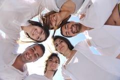 El grupo feliz de la gente tiene la diversión y funcionamiento en la playa Imagen de archivo libre de regalías