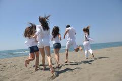 El grupo feliz de la gente tiene la diversión y funcionamiento en la playa Imágenes de archivo libres de regalías