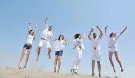 El grupo feliz de la gente tiene la diversión y funcionamiento en la playa Foto de archivo libre de regalías