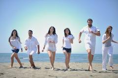 El grupo feliz de la gente tiene la diversión y funcionamiento en la playa Fotografía de archivo
