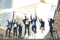 El grupo feliz del trabajo en equipo del negocio salta para arriba Celebración del concepto foto de archivo