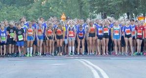 El grupo grande de muchachas corrientes y los muchachos en el comienzo alinean Imagen de archivo