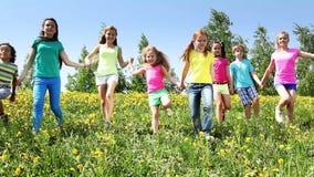 El grupo grande de niños corre en campo del diente de león