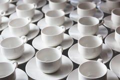 El grupo grande de tazas de té del café con leche arregló en filas Imagen de archivo