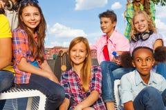 El grupo internacional de niños se sienta con los monopatines Foto de archivo libre de regalías