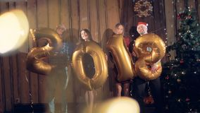 El grupo joven de amigos con 2018 figuras hincha la mirada en cámara Concepto 2018 de la fiesta de Navidad del Año Nuevo 4K almacen de metraje de vídeo