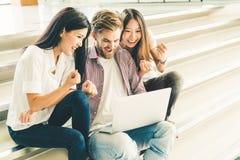 El grupo multiétnico de estudiantes universitarios o el equipo independiente casual joven celebra junto usando el ordenador portá imágenes de archivo libres de regalías