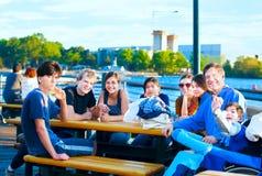 El grupo multiétnico de gente joven en la orilla del lago parquea Imagenes de archivo