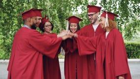 El grupo multiétnico feliz de los estudiantes de graduación está poniendo las palmas junta entonces que aplauden la celebración d almacen de video