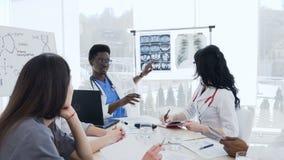 el grupo Multi-étnico de doctores profesionales con la radiografía del paciente es que resuelve y de discusión de la historia de  metrajes