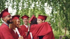 El grupo multi-étnico feliz de los estudiantes de graduación está abrazando y está haciendo alto-cinco después de ceremonia, de m almacen de video