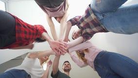 El grupo multicultural de amigos juntas apila sus manos, opinión inferior gente sonriente almacen de video