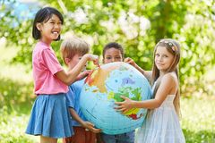 El grupo multicultural de ni?os sostiene el globo del mundo imágenes de archivo libres de regalías