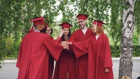 El grupo multirracial alegre de los estudiantes de graduación está poniendo las manos juntas entonces que aplauden las manos que  metrajes