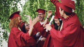 El grupo multirracial de estudiantes de la gente joven es el hacer alto-cinco el día de graduación que lleva los sombreros tradic almacen de metraje de vídeo