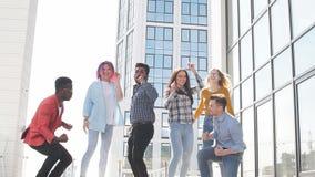 El grupo multirracial de hombres de negocios jovenes celebra un trato acertado bailando y saltando en el tejado almacen de metraje de vídeo