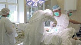 El grupo quirúrgico del hospital realiza una operación usando los instrumentos quirúrgicos estéril almacen de metraje de vídeo