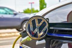 El GTE de Volkswagen Golf se carga en una estación de carga fotografía de archivo libre de regalías