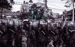 El guardia de la seguridad de la camisa roja se coloca delante del ejército del alboroto Foto de archivo libre de regalías