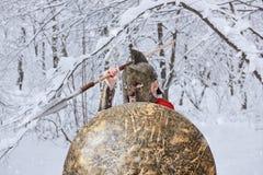 El guerrero espartano fuerte está esperando peligro en bosque nevoso Foto de archivo libre de regalías
