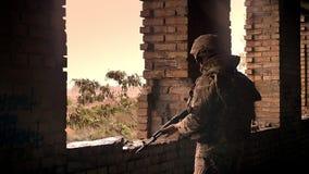 El guerrero resistente esperanzado en uniforme del camuflaje está sosteniendo el arma automático y se está colocando aislado en e almacen de video