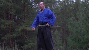 El guerrero semicalvo en un kimono azul se convierte en la postura que lucha con un katana almacen de metraje de vídeo