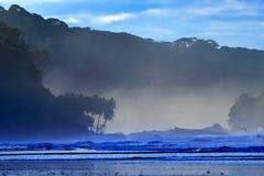 El guijarro y la playa arenosa durante salida del sol, con las ondas azul marino y las nubes anaranjadas, SE hermoso del crepúscu foto de archivo libre de regalías