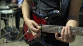 El guitarrista con una guitarra eléctrica roja juega música enrrollada con el batería en la calle Las manos masculinas toman un a metrajes
