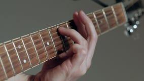 El guitarrista del primer juega en la guitarra en el fondo blanco almacen de video