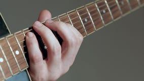 El guitarrista del primer juega en la guitarra en el fondo blanco almacen de metraje de vídeo