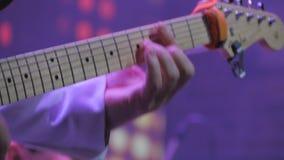 El guitarrista irreconocible toca la guitarra electrónica en cierre para arriba almacen de video